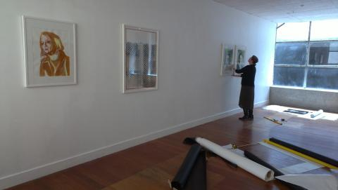 Andre Sampson helping with the hang; here seen with her own work and three portraits by Katrin Kampmann